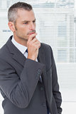 Thoughtful businessman posing with finger over his chin
