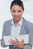 Happy businesswoman posing scrolling on her tablet pc