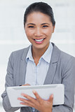 Smiling businesswoman posing scrolling on her tablet pc