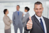 Smiling manager showing thumb up with employees in background