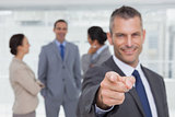 Cheerful businessman pointing at camera