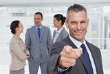 Cheerful businesman pointing at camera with colleagues on background