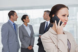 Businesswoman on the phone while colleagues talking together