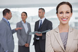 Smiling businesswoman posing while colleagues talking together