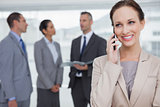 Smiling businesswoman calling while colleagues talking together
