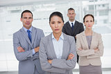 Serious work team posing crossing arms