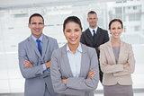 Cheerful work team posing crossing arms