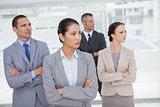 Stern work team crossing arms and looking away