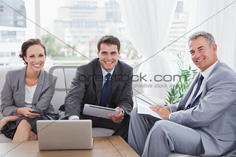 Business people smiling at camera while having a meeting
