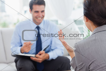 Smiling businessman talking to his colleague