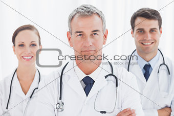 Cheerful doctors posing together crossing arms