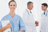 Smiling surgeon posing while doctors talking on background