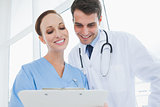 Cheerful doctor and surgeon viewing documents together