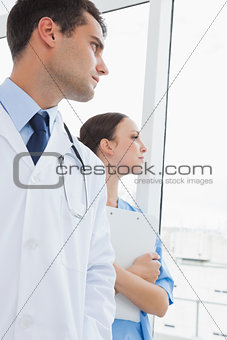 Thoughtful doctor and surgeon looking through the window