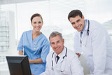 Cheerful doctors and surgeon looking at camera while working together