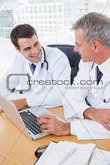 Doctors working together on laptop