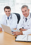 Doctors posing while working together on laptop