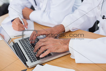 Close up on doctors hands typing on laptop
