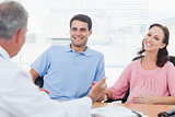 Smiling couple expecting baby consulting doctor