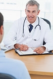 Cheerful doctor prescribing drug to his patient