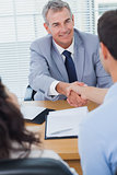 Smiling real estate agent shaking hands with his new buyer
