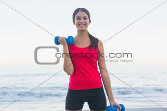 Cheerful sporty woman exercising with dumbbells