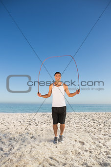 Smiling sporty man jumping rope