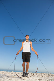 Cheerful sporty man jumping rope