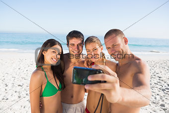 Smiling friends taking pictures of themselves