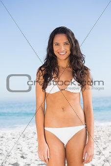 Smiling pretty brunette posing in white bikini