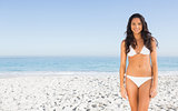 Happy sexy brunette posing in white bikini