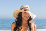 Attractive dark haired woman with straw hat posing