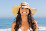 Smiling attractive dark haired woman wearing straw hat posing