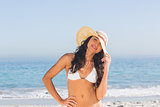 Relaxed attractive dark haired woman wearing straw hat posing