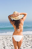Back of attractive young woman wearing straw hat posing