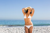 Cheerful attractive young woman wearing straw hat posing