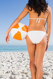 Back of womans perfect body holding beach ball