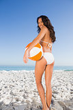 Smiling sexy brunette in white bikini holding beach ball