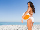 Smiling sexy brunette in white bikini with beach ball