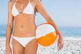 Sexy female body in white bikini with beach ball