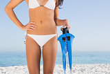 Perfect female body in white bikini holding fins