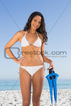 Beautiful brown haired woman in white bikini holding fins