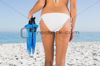 Perfect feminine buttocks of young woman holding fins