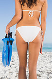 Perfect feminine buttocks of slim young woman holding fins