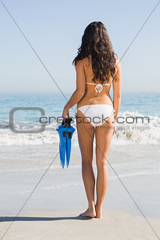 Back of slim young woman holding fins