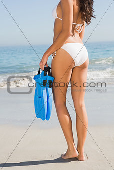 Perfect body of young woman holding fins