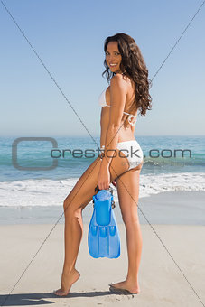 Slim young woman posing while holding fins