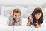Siblings lying on bed playing video games