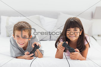 Smiling siblings lying on bed playing video games together