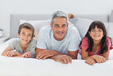 Father with his children lying on bed